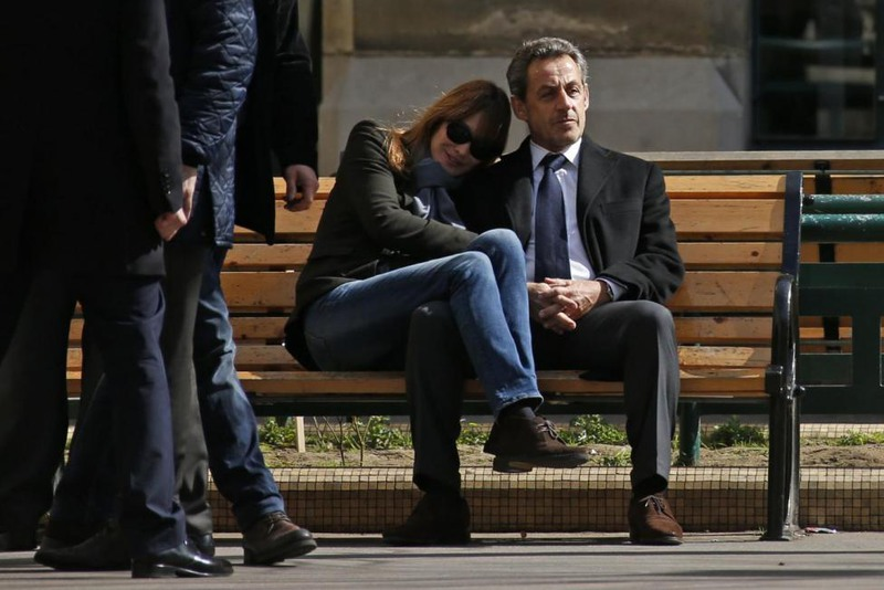 1 Benoit Tessier. Former French President Nicolas Sarkozy sits on a bench with his wife Carla Bruni-Sarkozy in Paris, March 23, 2014.