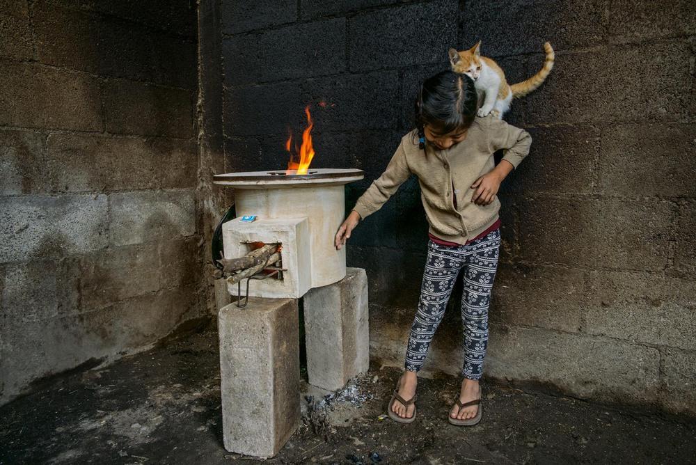 23 Автор: Линн Джонсон. 7-летняя Таня Лопес играет с кошкой в комнате с покрытыми сажей стенами из-за использования старого открытого камина.