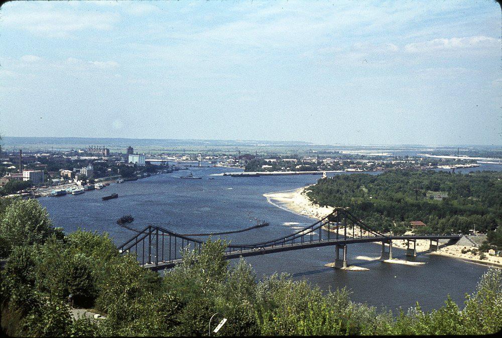 3 За Подольской ТЭЦ и станцией Петровка город уже заканчивался. Видна гора, на которой расположен старый Вышгород. Как раз в это время там строилась Киевская ГЭС. Напротив центрального пляжа работает земснаряд. Нет ещё ни Оболони, ни Троещины.