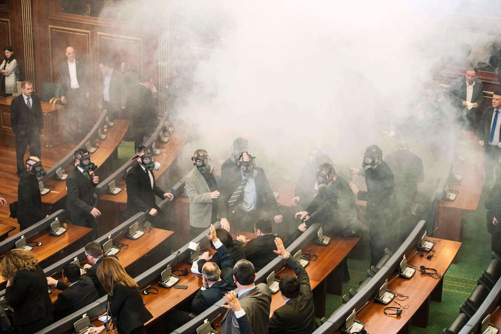 10 Февраль. Security officers wore gas masks while inspecting the Parliament building after opposition lawmakers disrupted a session by releasing tear gas. Armend Nimani