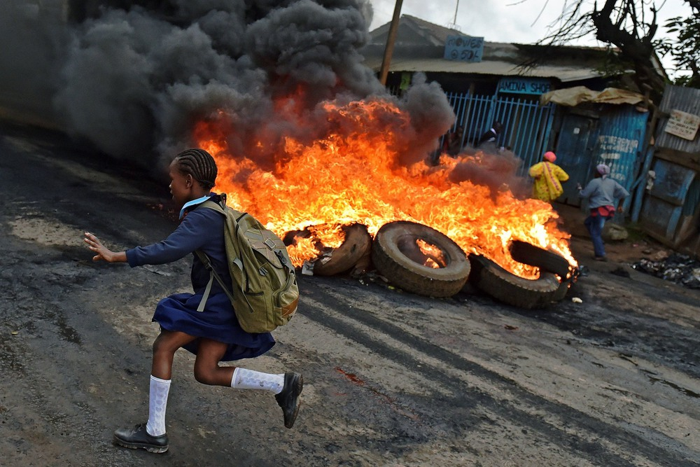 20 Май. A schoolgirl ran past a burning barricade set up by opposition supporters critical of the country's election commission.Carl De Souza/Agence France-Presse