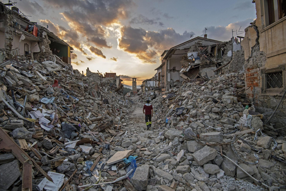 34 Сентябрь. A rescuer walked through rubble after an earthquake struck an area about 100 miles northeast of Rome, killing nearly 300 people.Alessandro Di Meo
