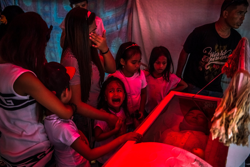 "38 Октябрь. Jimji, 6, cried out in anguish, saying ""Papa!"" as workers prepared to move the body of her slain father for burial. President Rodrigo Duterte of the Philippines oversaw a brutal campaign against suspected drug users or dealers, with a call to ""slaughter them all.""Daniel Berehulak"