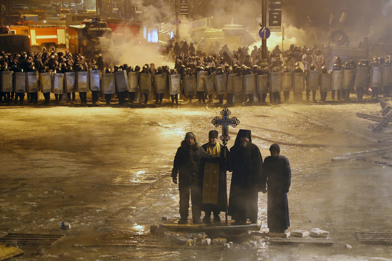 1 Orthodox priests prayed as they stood between pro-European Union activists and police lines. KIEV, UKRAINE. 01/24/2014. Sergei Grits/Associated Press/