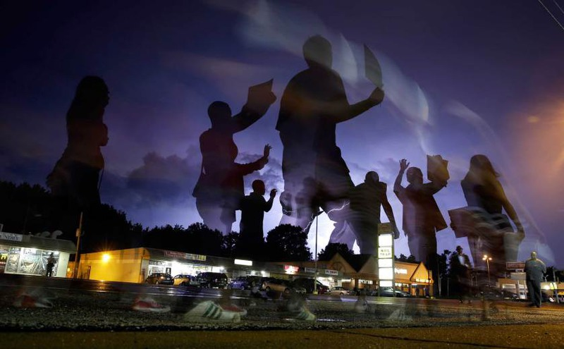 1 Автор - JEFF ROBERSON—AP. Protesters march in the street as lightning flashes in the distance in Ferguson, Mo, Aug. 20, 2014.