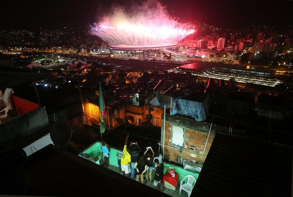 11 августа, Рио-де-Жанейро, Бразилия. Жители фавел любуются салютом на стадионе «Маракана», венчающим церемонию открытия Олимпийских игр. Фото: Mario Tama / Getty Images.