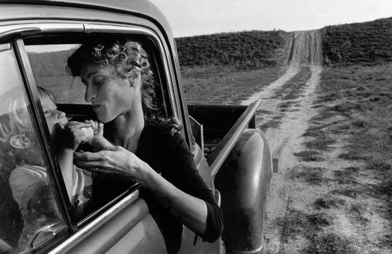 CANADA. Lambton County, Ontario. Мой старший сын Moses TOWELL ест дикую грушу в то время, как Анн сидит в грузовике 1951-го года. Это семейная машина, которую я купил за 200$ и починил на собственный манер. 1983 © Larry Towell / Magnum Photos