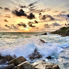Інший захід сонця, бризки хвиль, каміння та пальми.