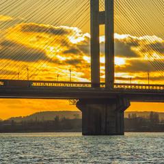 Хмари зворохобилися за мостом проти ночі – сонце ховається за ними.