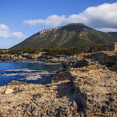 На кам'янистому березі моря велика гора з хмарами є.