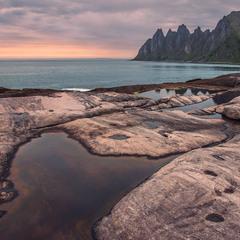 Теплий вечір на морі після дощу посеред каміння.