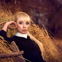 Beautiful young blonde standing near haystack