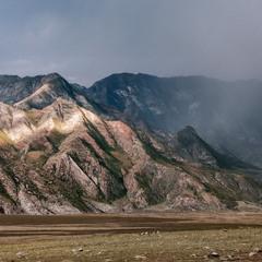 Осень.... Справа идет дождь. Слева, пробившееся солнце высветило участок гор....